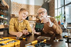Smart skillful man showing what to do. Be attentive. Smart nice skillful men holding a broken electronic device and showing his grandson what to do while fixing Royalty Free Stock Image