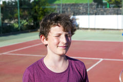 Smart smiling boy  at the outdoor tennis court Stock Image