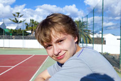 Smart smiling boy at the outdoor tennis court Stock Photos