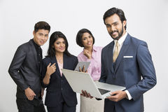 Smart smiling businessman working in laptop with his team business people. Happy smart businessman working in laptop with his team business people on white Stock Photography
