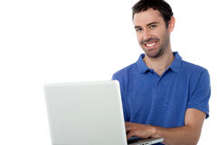 Smart smiling guy working on laptop Royalty Free Stock Images
