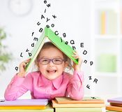 Smart smiling kid in glasses taking refuge under. Happy kid in glasses under roof made from book hiding from falling letters Royalty Free Stock Photography