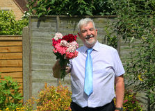 Smart smiling man giving bunch of flowers. A smart well dressed senior man smiling and giving a bunch of flowers Royalty Free Stock Image