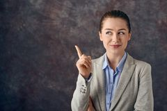 Smart smiling young professional or business woman pointing her finger in the air. With a pleased smile as she finds a solution to a problem or thinks of a Stock Photo