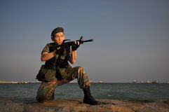 Smart Soldier Defending The Country. Smart Asian soldier in uniform holding rifle by the sea stock images