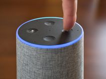 Smart speaker artificial intelligence assistant voice control blue ring. Finger stock photo