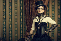 Smart steampunk. Portrait of a beautiful steampunk woman over vintage background royalty free stock photo