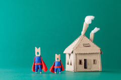 Smart and strong clothespin superheroes  cardboard house. Big small super team characters on green background. soft Royalty Free Stock Photography
