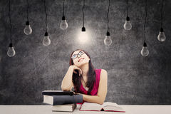 Smart student. Portrait of smart female college student with books and bright light bulb above her head as a symbol of bright ideas Royalty Free Stock Image