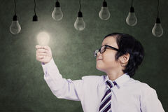 Smart student with bright idea. Smart asian child holding a lit bulb under lamps Royalty Free Stock Photo