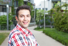 Smart student with checked shirt laughing at camera. Smart student with checked shirt standing on campus and laughing at camera with university  building, meadow Royalty Free Stock Photo