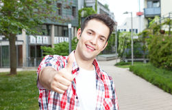 Smart student with checked shirt showing thumb up. Smart student with checked shirt standing on campus and showing thumb up with university building, meadow and Royalty Free Stock Photos
