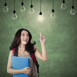 Smart student choosing a bright light bulb. Image of a clever high school student getting idea and choose the bright light bulb in the classroom Stock Photography
