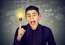 Smart student with idea light bulb science formulas on blackboard. Smart student with bright idea light bulb and high school maths and science formulas on Stock Photo