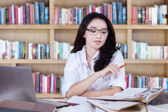 Smart student learns with books in library Stock Image