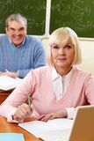 Smart student. Portrait of blond female looking at camera with senior men on background Stock Photos
