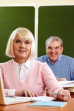 Smart student. Portrait of blond female looking at camera with senior men on background Royalty Free Stock Photos