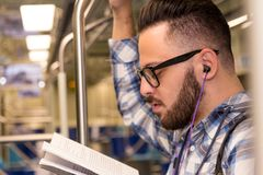 Smart student reading a book on a subway listening to music. Con stock image