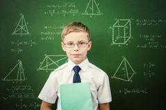 Smart student or schoolboy with a notebook standing near blackboard Stock Image