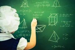 Smart student or schoolgirl drawing mathematic formula at blackboard Stock Photo