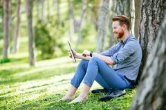 Student studying in park. Smart student studying outdoors in green park Stock Photo