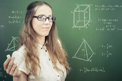 Smart student or teacher drawing mathematic formula at blackboard. Dressed in university uniform and sunglasses, scribbled with chalk - formulas and drawing royalty free stock image