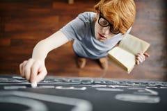 Smart Student Writing on Blackboard Royalty Free Stock Photos