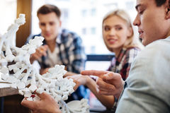 Smart students getting ready for genetics classes. Future scolars. Selective focus of DNA model while cheerful smart students discussing project and studying royalty free stock photos