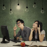 Smart students thinking a right solution. Portrait of smart college students with books and bright light bulb above their head as a symbol of bright ideas Royalty Free Stock Image