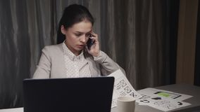 Young woman talking on smart phone at home office. Smart and successful woman sitting behind table with modern laptop computer. Young freelancer working at home stock footage