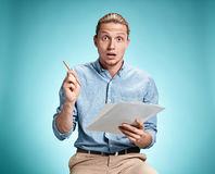 Smart surprised student with great idea holding sheets of paper Royalty Free Stock Photography