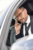 Smart taxi driver making a phonecall. Taxi driver receiving phonecall from client Stock Image