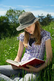 Smart Teenage Girl Sitting In The Grass With Legs Crossed Reading A Book Outdoors Royalty Free Stock Photography