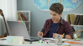Smart teenage kid diligently doing homework tasks to achieve success in future stock footage