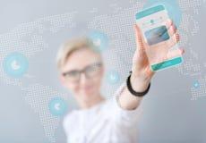 Smart telefon för angenämt kvinnainnehav fotografering för bildbyråer