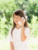 Smart telefon för Asien flickabruk i trädgård Arkivbilder