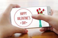 Smart telefon för handinnehav med lycklig dag för valentin` s på skärmen Arkivfoto