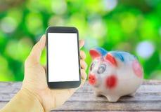Smart telefon för handinnehav på spargrisen på trätabellbackgroun Fotografering för Bildbyråer