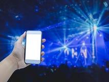 Smart telefon för handinnehav på suddig konsert royaltyfri foto
