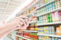 Smart telefon för handinnehav på supermarketlbakgrunder Royaltyfria Foton