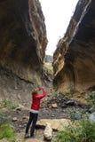 Smart telefon för kvinnainnehav och tafoto på den sceniska klippan inom kanjonen i panelljus Turist- dragning i det majestätiska  Arkivbild