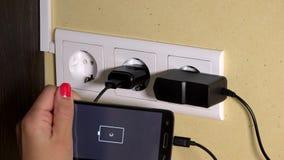 Smart telefon för kvinnlig handpropp till vägguppladdaren och håll i hand stock video