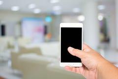 Smart telefon för manhåll på lobbyen som ser doktorsbakgrund Arkivbilder