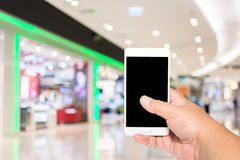 Smart telefon för manhåll på suddigt av folk som shoppar i shoppinggalleriabakgrund Arkivbild