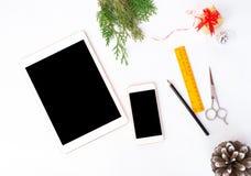 Smart telefon för minnestavla på den vita skärmen för modell i jultid Julgran garneringar i bakgrund Arkivbild