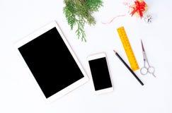 Smart telefon för minnestavla på den vita skärmen för modell i jultid Julgran garneringar i bakgrund Royaltyfri Bild