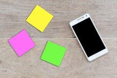 Smart telefon för mobil med notepaden på wood bakgrund, Fotografering för Bildbyråer
