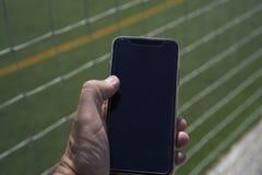 Smart telefon för svart i en hand royaltyfri bild