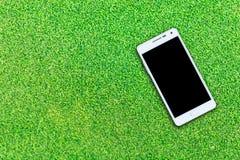 Smart telefon för vit på gräsbakgrund Fotografering för Bildbyråer