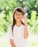 Smart telefon för Asien flickabruk i trädgård Royaltyfri Bild